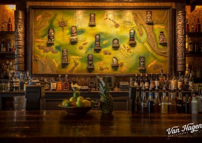 Image of the back bar from Latitude 29 (New Orleans) shows a large map populated with tiki mugs of various regions